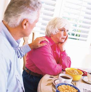 Senior couple at breakfast table , woman looking sad, man with hand on her shoulder.