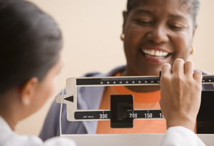 Woman standing on scale at doctor's office, smiling, happy.