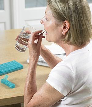 Senior woman taking pill with water.