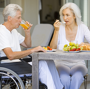 Woman and man in wheelchair eating breakfast.