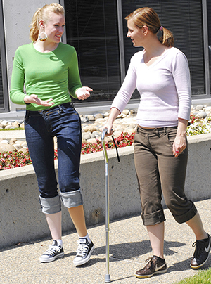 Two women walking, one is using a cane.