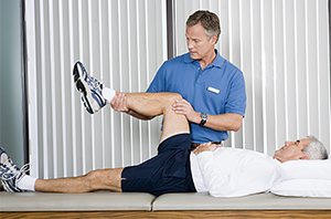 Physical therapist working with older man.