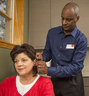 Healthcare provider fitting woman with hearing aid.