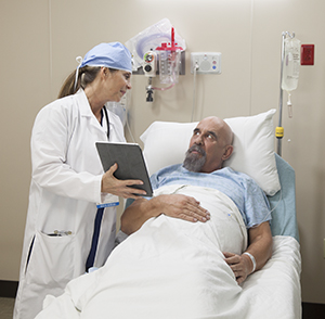 Healthcare provider talking with man in pre-op hospital room