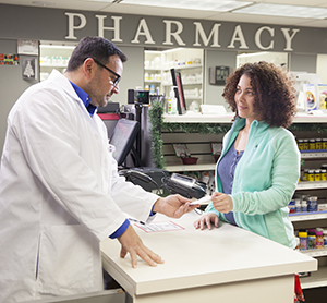 Pharmacist talking with woman at pharmacy counter