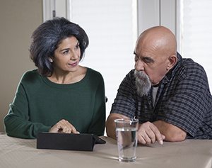 Man and woman sitting at table looking at electronic tablet.
