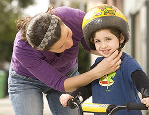 Woman putting helmet on preschooler boy on bike.