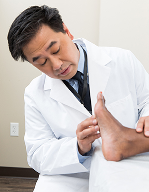 Healthcare provider examining woman's foot.