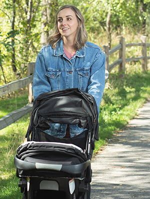 Woman walking outdoors with baby in stroller.